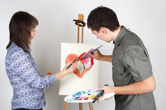 Man and girl painting red heart Stock Image