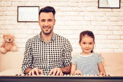 Man and Girl Play Piano. Playing Piano Together. Piano and Guitar. Father and Daughter on Sofa. Spend Time Together. Father`s day. Man Play with Girl. White royalty free stock photography