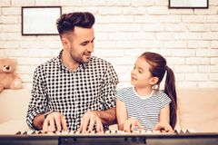 Man and Girl Play Piano. Play Piano Together. Father and Daughter on Sofa. Spend Time Together. Father`s day. Man Play with Girl. White Interior. Girl wiht Man stock photography