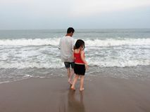Man & girl playing in the waves. Man and girl playing in the waves at the beach near evening in summer stock photography
