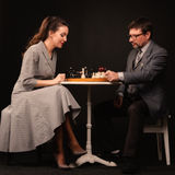 A man with a girl plays chess and smokes a pipe on a dark backgr. A men with a girl plays chess and smokes a pipe on a dark background Stock Photo