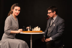 A man with a girl plays chess and smokes a pipe on a dark backgr. A men with a girl plays chess and smokes a pipe on a dark background Royalty Free Stock Images