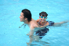 Man & girl in the pool. Man & girl playing in the swimming pool Royalty Free Stock Photos