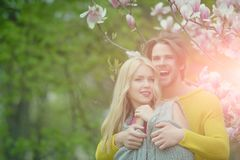 Man with girl or pretty woman at blossoming magnolia stock images