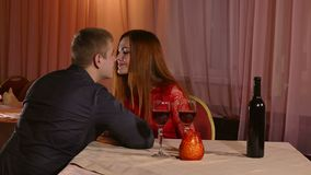 Man and girl romantic evening in restaurant kiss drinking love woman wine, Valentine's Day video 4K. Man and  girl romantic evening in restaurant kiss drinking stock video