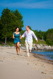 Man and girl running along coast of blue sea Stock Images