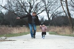 Man and Girl Running on Asphalt Road stock photos