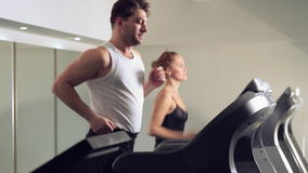 A man and a girl running on the treadmill
