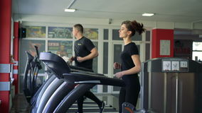 A man and a girl running on the treadmill at the gym. 4k. A man and a girl running on the treadmill at the gym stock footage