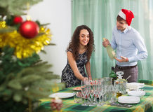 Man and girl serving Christmas table for  guests Royalty Free Stock Photography