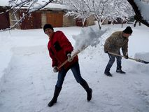 People clear away the snow shovels after heavy snowfall stock image