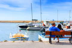A man and a girl are sitting on a bench in the port and waiting for a girl against a background of white yachts and boats Royalty Free Stock Images