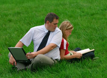 Man and girl sitting in the grass. Man with laptop and girl with book sitting on the grass Stock Images