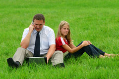 Man and girl sitting in the grass. Man with laptop and girl sitting on the grass Stock Images