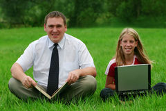 Man and girl sitting on the grass. Man with a book and girl with laptop sitting on the grass Royalty Free Stock Photos