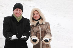 Man and girl smiling and holding snowballs Royalty Free Stock Photography