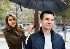 Man and girl smiling under umbrella outdoors Stock Images