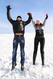 Man and girl on snowy area and smiling. Young man and girl jump on snowy area and smiling, holding for hands, looking at camera Stock Images