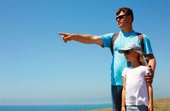 Man and girl standing in a beach sea. The man points to a Royalty Free Stock Photo
