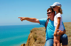Man and girl standing in a  beach sea. The man points to a Royalty Free Stock Photography