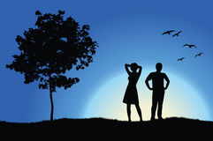 Man and girl standing on hill near tree Royalty Free Stock Photo