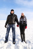 Man and girl standing on snowy area. Young man and girl standing on snowy area, holding for hands and smiling, looking at camera Stock Image