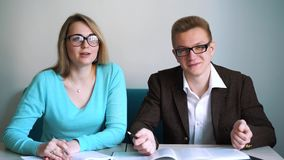 Man and girl students sitting at the table, answer questions. Man and girl students sitting at the table, answer questions stock video footage