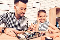 Man and Girl with Tool. Father and Daughter on Sofa. Spend Time Together. Father`s day. White Interior. Review Device. Spare Part. S on Table. Measure with Tape stock photo