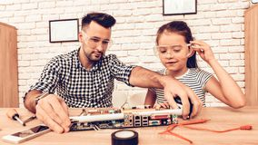 Father and Daughter Repair Device on Table at Home royalty free stock photography