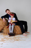 Man and girl in Ukrainian national dress with a book about busin. Man and girl in Ukrainian national dress and jeans sitting on a haystack with a book about Stock Photography