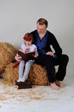 Man and girl in Ukrainian national dress with a book about busin. Man and girl in Ukrainian national dress and jeans sitting on a haystack with a book about Royalty Free Stock Images
