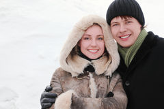 Man and girl in warm dress smiling, embracing Stock Photography