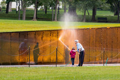 Man and girl washing wall at Vietnam memorial Stock Photos