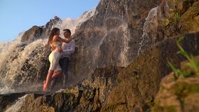 A man and a girl in wet clothes stand among the rocks under the waterfall during the sunset on a summer day, slow motion. Couple hugs under a waterfall among stock footage