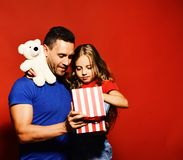 Man and girl with white teddy bear on red background. Surprise or fathers day present concept. Daughter and dad look into gift box. Father and child with royalty free stock photo