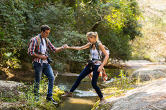 Man girlfriend crossing stream. Young men helping girlfriend crossing stream at mountain valley Stock Photography