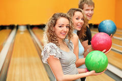 Man and girls made row of ball in bowling club Stock Photography