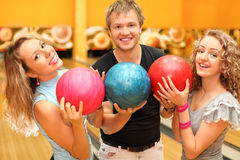 Man and girls made row of balls in bowling club Stock Images