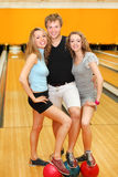 Man and girls put feet on balls in bowling club Royalty Free Stock Photo