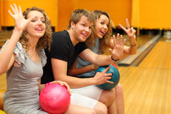 Man and girls sit, hold balls  in bowling club Stock Image