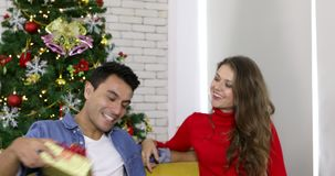 Man give gift to girlfriend, she kissing him. Christmas tree at foreground, then scene is blur and turn to clear, happy Caucasian couple sitting together, man stock footage