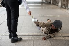 Man give money to disabled homeless man. Business man giving one US dollar bill money to old disabled homeless man lying on city walk in urban town. Poverty for royalty free stock image