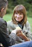 Man gives apple to woman Stock Photo