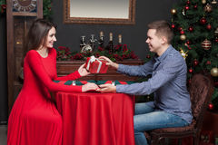 Man gives an attractive gift to beautiful woman Stock Photography
