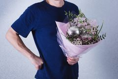 A man gives a bouquet of flowers and ladles. concept of patriarchal society and gender inequality. Sexism and feminism.  royalty free stock photography