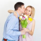Man gives a bouquet of flowers to woman. Husband gives a gift to his wife. Mother`s day. Valentines day Stock Images