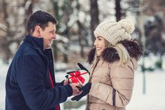 Man gives a box with a gift to his girlfriend, romantic surprise royalty free stock images