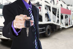 Man gives a car key with trailer truck background Royalty Free Stock Photo