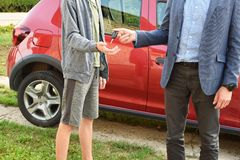 Man gives car keys to teen boy royalty free stock image