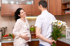 Man gives chamomile flowers to pregnant woman, couple in kitchen interior with fresh fruits and vegetables, healthy food concept Royalty Free Stock Images